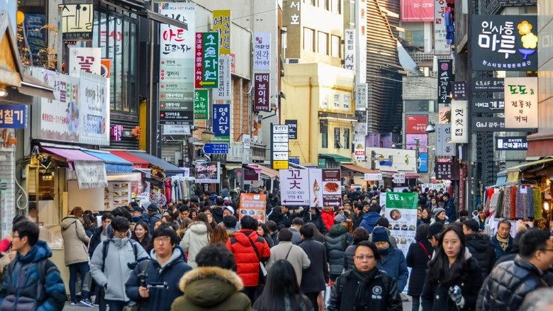 A crowded street in the Dongdaemun District of South Korea. There are many storefronts and people. Photo taken during a cold winter day.
