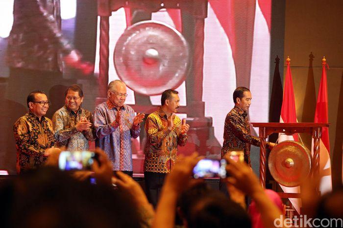 Jokowi memukul gong sebagai tanda dimulainya Rapat Kerja Nasional Asosiasi Pengelola Pasar Indonesia (Asparindo) di Hotel Aryaduta, Jakarta, Rabu (12/12/2018).