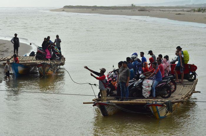 Warga bersama kendaraan bermotor menyeberangi sungai menggunakan perahu di Sungai Muara Cipatujah, Kabupaten Tasikmalaya, Jawa Barat. Antara Foto/Adeng Bustomi.