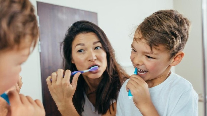 Mother and son brushing teeth in bathroom. Woman with her son brushing teeth together and looking in mirror.