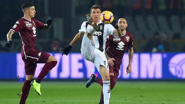 Mario Mandzukic mencoba mengontrol bola dikawal ketat pemain Torino. (
