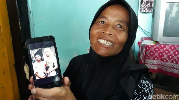 Juwariyah menunjukkan foto pernikahan anaknya dengan Polly.