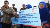 Kepala Eksekutif Pengawas Perbankan OJK Heru Kristiyana (kiri) menyerahkan bantuan CSR secara simbolis kepada Kelompok Usaha Desa Arjowilangun, Kabupaten Malang. Foto: dok. BRI