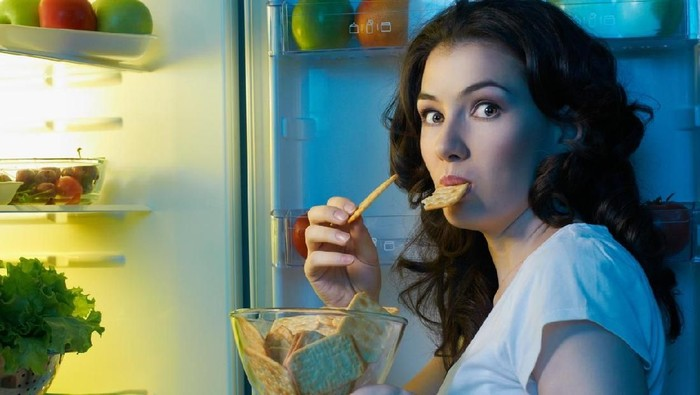 a hungry girl opens the fridge