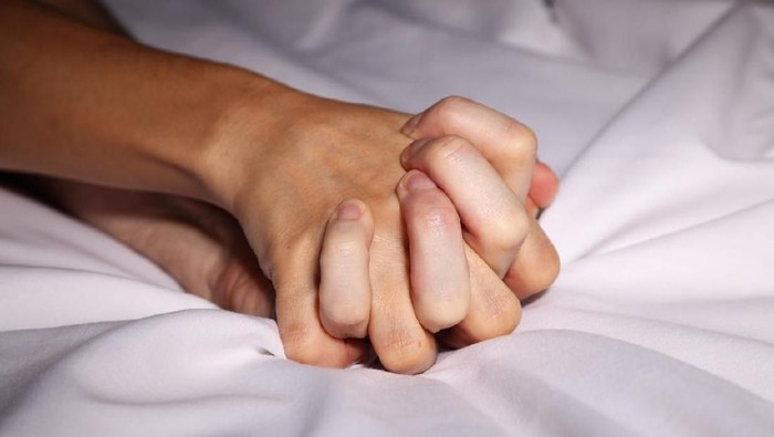 Couple in bed holding hands passionately