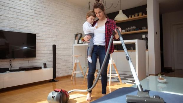 One young woman holding her baby, using vacuum cleaner for cleaninig her house.