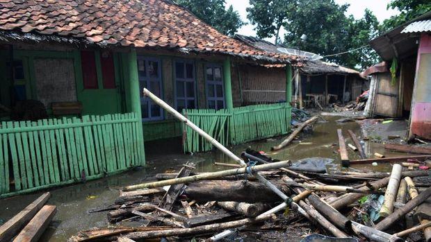 Tumpukan kayu dan bambu yang terhempas gelombang tsunami berserakan di halaman rumah di Kampung Sindangsari, Kecamatan Panimbang, Pandeglang, Banten, Minggu (23/12/2018).
