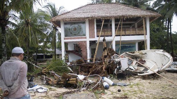 Warga berada di depan bangunan yang terdampak bencana Tsunami di Pantai Tanjung Lesung, Banten, Jawa Barat, Minggu (23/12/2018)