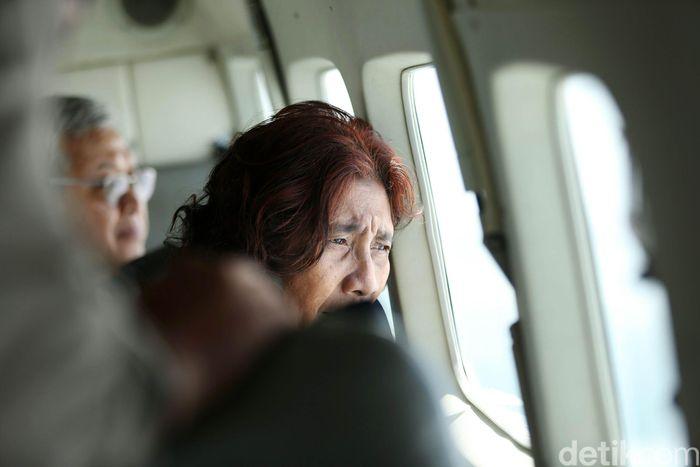 Susi memantau kerusakan akibat tsunami yang meluluh-lantakkan pesisir laut Banten dari dalam pesawat.