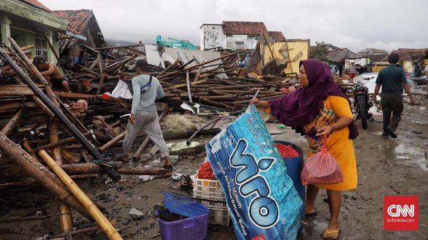 Warga memunguti barang-barang dari reruntuhan sisa terjangan tsunami di desa Sumberjaya, kecamatan Sumur, Pandeglang, Banten, ( 24/12).