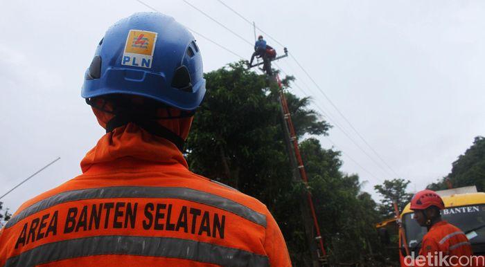 Petugas bahu membahu memperbaiki jaringan listrik yang hancur akibat tsunami.