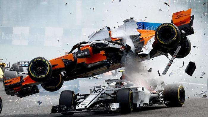 Pebalap McLaren Fernando Alonso terbang bersama mobilnya usai ditabrak sesama pebalap Charles Leclerc di GP Belgia Agustus lalu. (Francois Lenoir/Reuters)