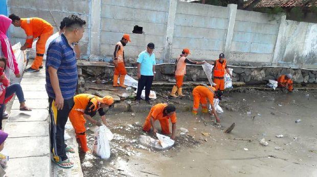 Petugas dan warga bersih-bersih limbah diduga material vulkanik Gunung Anak Krakatau di Kepulauan Seribu, Jumat (28/12/2018)