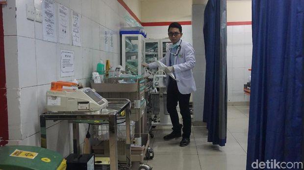 Seorang dokter sedang bersiap menangani pasien.