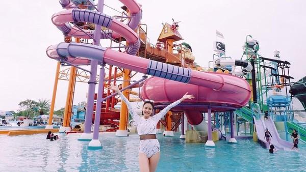 Lihat senyum lebar Milin saat main air di waterpark Thailand ini. Sepertinya seru main perosotan seperti yang ada di belakang Milin. (Instagram/@milinb3rry)