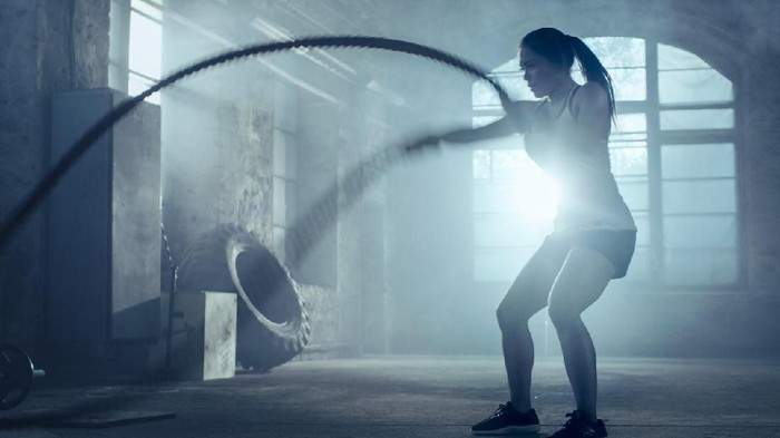 Strong Athletic Woman Exercises with Battle Ropes as Part of Her Cross Fitness Gym Workout Routine. Shes Covered in Sweat and Training Takes Place in a Abandoned Factory Remodeled into Gym.