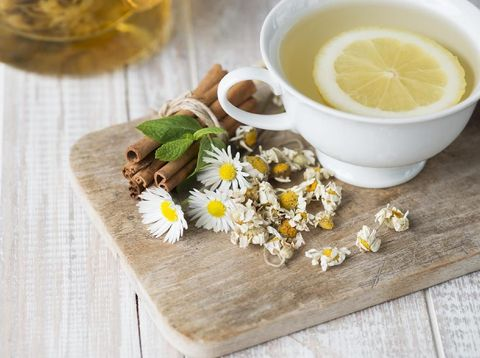 Herbal tea with lemon slice on a white wooden table with chamomile plants and cinnamon.
