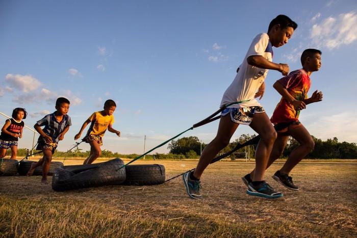 Anak-anak menjalani latihan untuk menguatkan kaki dengan berlari menarik ban bekas. (Foto: Paula Bronstein/Getty Images)