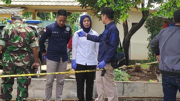 Seorang anggota Labfor Polri bersarung tangan memegang senjata api milik korban