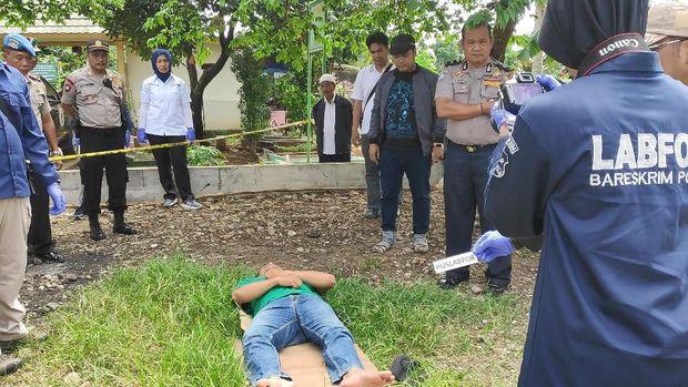 Seorang pria berbaring di atas rumput memerankan almarhum.