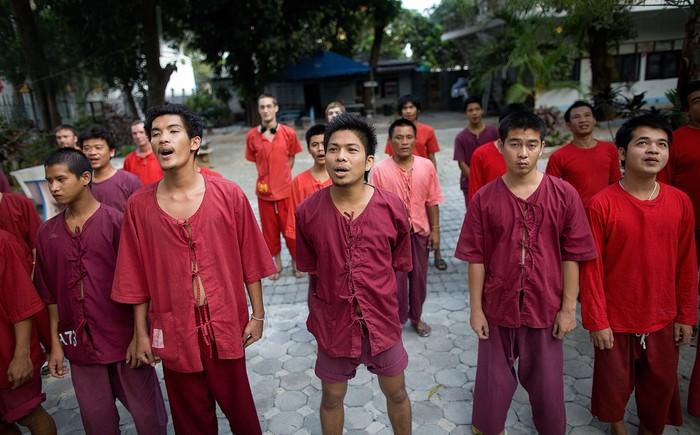 Para peserta program detoksifikasi di kuil Wat Thamkrabok berbaris menyanyikan lagu nasional Thailand. Peserta diharapkan mengikuti program minimal sampai seminggu. (Foto: Paula Bronstein/Getty Images)