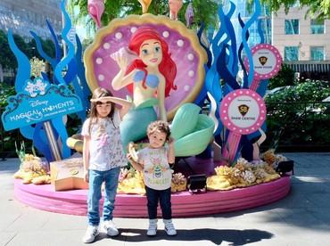 Meskipun silau, tetap eksis nih si cantik Elea dan Cimbot, panggilan sayang si bungsu. Dengan gaya masing-masing pose di depan patung Little Mermaid di Disneyland Singapore. (Foto: Instagram @ussypratama)