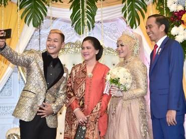Kalau ini saat Iriana dan Jokowi hadir di resepsi pernikahan pasangan atlet pencak silat Indonesia, Hanifan Yunadi Kusumah dan Pipiet Kamelia. Jangan lupa selfie! (Foto: detikcom)