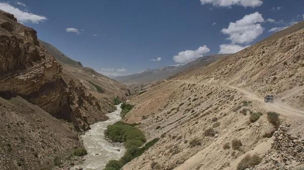 Rute Pamir Highway melewati Koridor Wakhan dan mengikuti Sungai Panj yang memisahkan Afghanistan dan Tajikistan. Pemukiman kecil Muslim Ismailiyah menghiasi kedua sisi jalur sungai (Dave Stamboulis/BBC Travel)