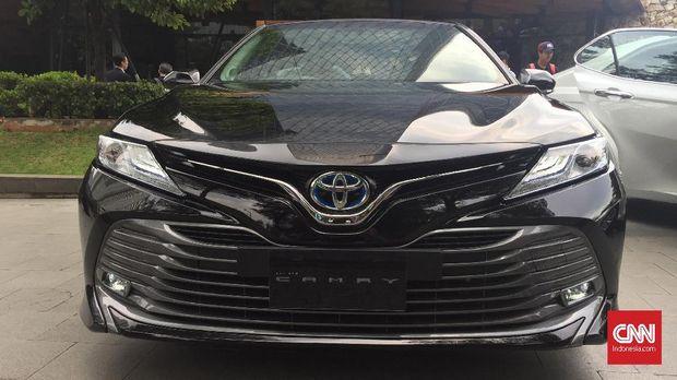 Toyota Camry tipe hybrid menawarkan logo dengan aksen biru.