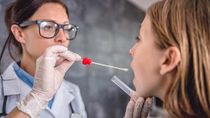 Female pediatrician using a swab to take a sample from a patients throat