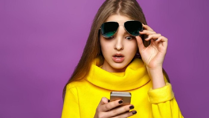 Portrait surprised young girl from message on smartphone in brightly yellow sweater, isolate on a violet background