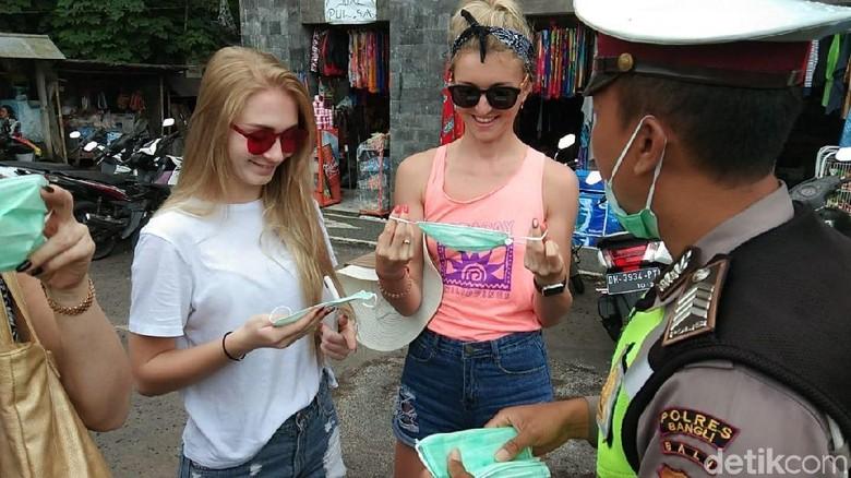 Foto: Polisi membagikan masker untuk wisatawan (Aditya Mardiastuti/detikTravel)