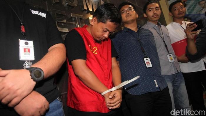 Iwan Kurniawan memakai rompi merah tertunduk lesu saat ditangkap polisi (lamhot/detikcom)