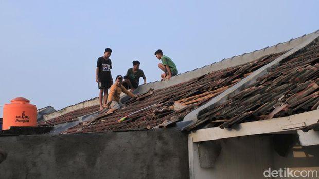 Warga tengah memperbaiki atap rumah yang rusak