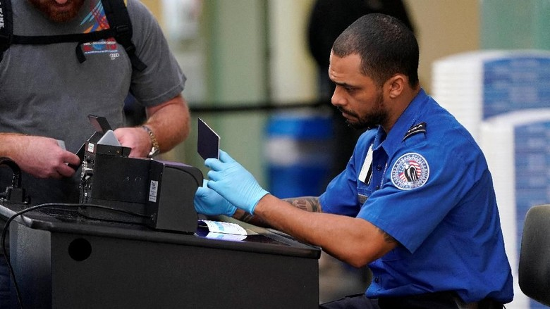An employee with the Transportation Security Administration (TSA) checks the documents of a traveler at Reagan National Airport in Washington, U.S., January 6, 2019.      REUTERS/Joshua Roberts