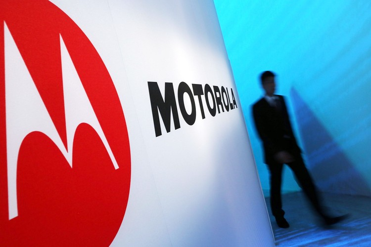 NEW YORK, NY - SEPTEMBER 05: A person walks by a Motorola sign at the launch of three new Motorola smartphones under its Razr brand that will become available for Verizon customers on September 5, 2012 in New York City. The new phones, the Droid Razr HD, the Razr M and the Razr Maxx HD, will all use Googles Android operating system. Motorola Mobility was acquired by Google in August of 2011.  (Photo by Spencer Platt/Getty Images)