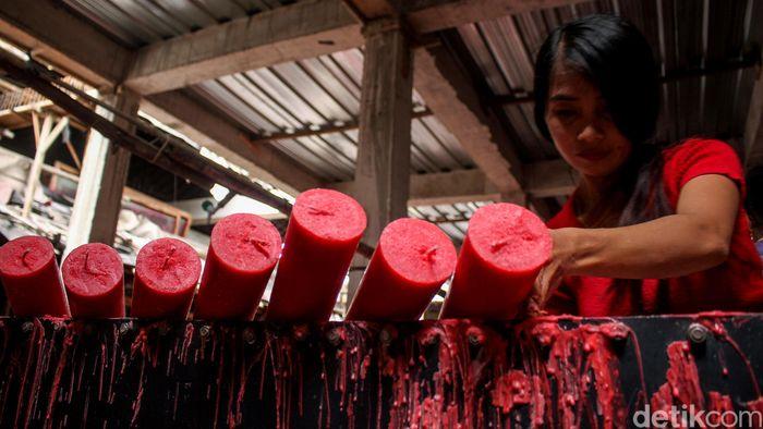 Seorang pekerja tengah menyelesaikan proses produksi lilin.