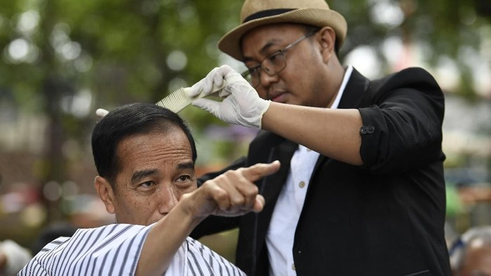 Herman saat mencukur rambut Jokowi di Garut. (Foto: ANTARA FOTO/Puspa Perwitasari)