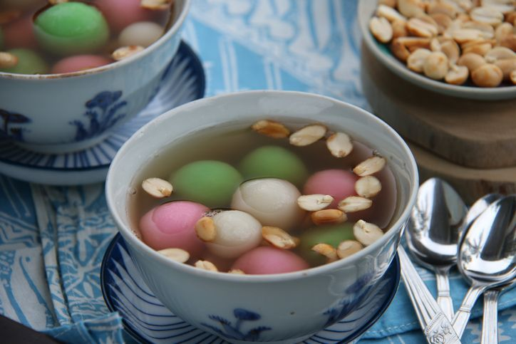 A Chinese Peranakan dessert of glutinous rice balls in warm ginger soup. Served in vintage ceramic bowls with extra peanuts, also in vintage saucer. A few teaspoons are placed on a folded batik napkin. The meal is arranged on a rustic wooden table.