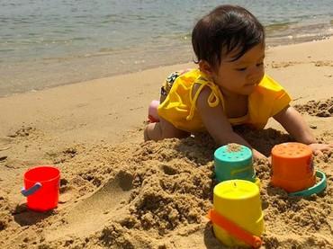 Bri nampaknya lagi seru banget nih mainan pasir. Menyusun ember kecil warna-warni membuatnya jadi lebih antusias bermain di pantai. (Foto: Instagram: @septriasaacha)