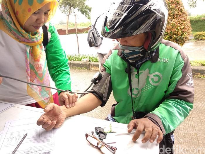 Driver ojol pun nggak mau kalah lho, demi kesehatan ia mampir sebentar untuk memeriksakan kesehatannya. (Foto: Widiya Wiyanti/detikHealth)