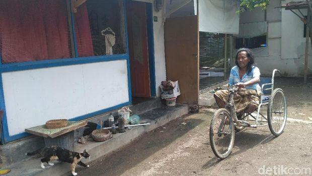 Edi menggunakan sepeda roda tiga untuk membantu berpindah tempat