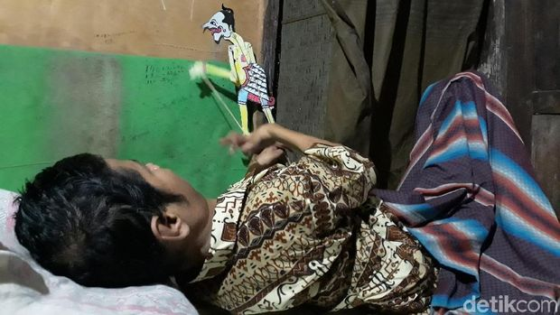 Mbah Un saat memainkan wayangnya di sela belajar bersama di rumahnya.