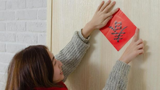 Young asian woman pastes spring couplet. It is the tradition of Chinese culture to stick spring couplet to the doors for Chinese New Year. The word on the spring couplet means