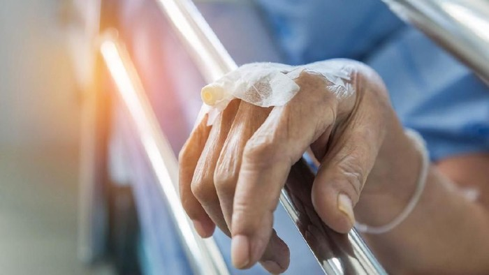 Close up hand of elderly patient with intravenous catheter for injection plug in hand during lying in hospital ward room