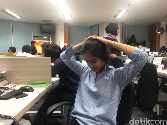 Tarik kedua tangan ke bagian kepala. Dalam keadaan duduk di kursi kantor, aktivitas gerak ini tentu saja sangat mudah untuk dilakukan. Untuk melancarkan peredaran darah serta meregangkan otot, lakukanlah gerakan ini selama kurang lebih 3 menit. (Foto: Kireina/detikHealth)
