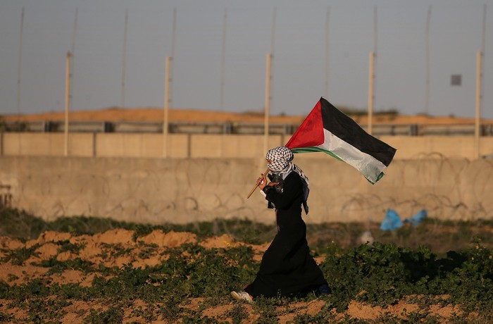 A demonstrator holds a Palestinian flag during a protest at the Israel-Gaza border fence, in the southern Gaza Strip January 18, 2019. REUTERS/Ibraheem Abu Mustafa