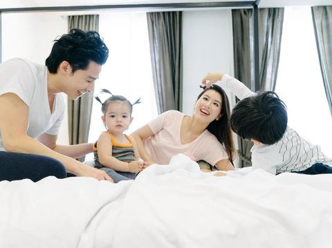 Happy Thai family waking up in the morning, mum and dad having fun in bed with children