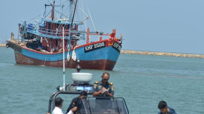 Petugas pengawasan perikanan menggunakan perahu motor mengawal dua unit kapal ikan berbendera Malaysia yang ditangkap di perairan Selat Melaka saat digiring ke Pelabuhan Perikanan Koetaraja, Banda Aceh, Selasa (5/2/2019).  (Foto: dok. Antara Foto)