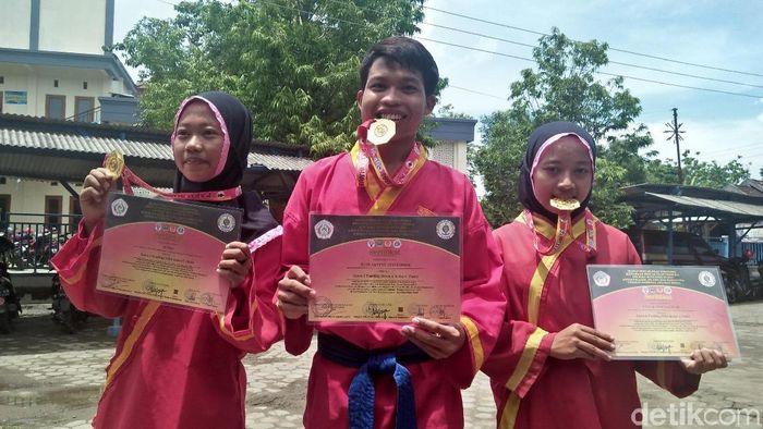 Putri, Luluk, dan Rudi berhasil menggondol medali emas dari kejuaraan pencak silat Paku Bumi Terbuka 2019. (Arif Syaefudin/detikSport)